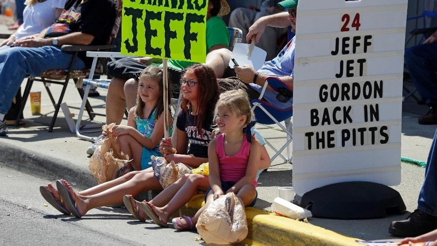 Fans sit on the curb as they await the arrival of NASCAR driver Jeff Gordon during parade in his honor in Pittsboro, Ind., Thursday, July 23, 2015. Gordon will drive in Sunday's Brickyard 400.  (AP Photo/Michael Conroy)