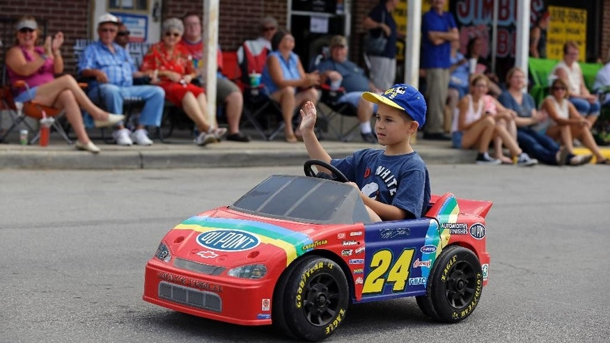 A fan waves as he  drives a replica of NASCAR driver Jeff Gordon's car in front of fans that lines the route of a parade to honor Gordon in Pittsboro, Ind., Thursday, July 23, 2015. Gordon will drive in Sunday's Brickyard 400.  (AP Photo/Michael Conroy)