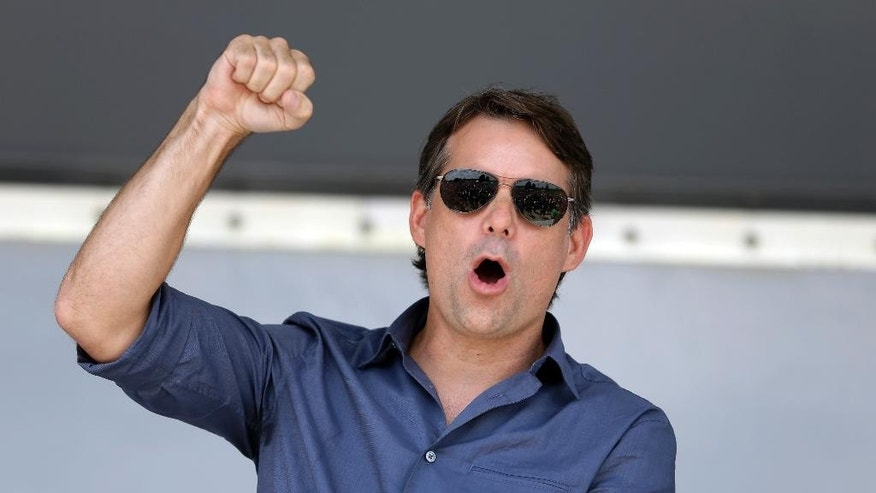 NASCAR driver Jeff Gordon pumps his fist as he takes the stage following a parade in his honor in Pittsboro, Ind., Thursday, July 23, 2015. Gordon will drive in Sunday's Brickyard 400.  (AP Photo/Michael Conroy)