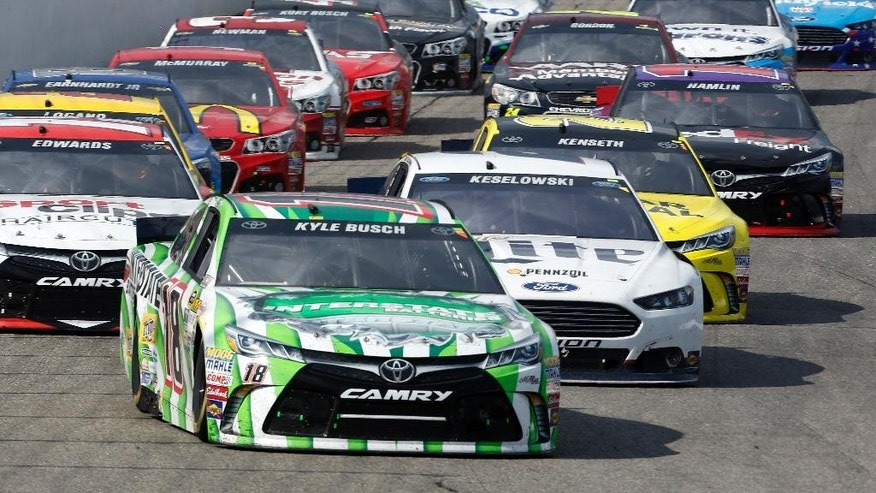 Kyle Busch (18) takes the lead on the restart during the the NASCAR Sprint Cup series auto race at New Hampshire Motor Speedway Sunday, July 19, 2015, in Loudon, N.H. Bush went on to win the race.  (AP Photo/Jim Cole)
