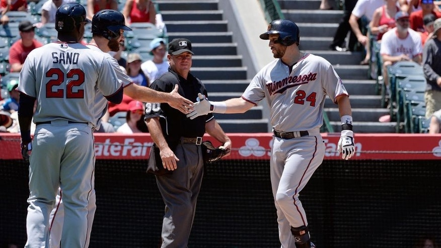 Jul 23, 2015; Anaheim, CA, USA; Minnesota Twins third baseman Trevor Plouffe (24) celebrates with Minnesota Twins first baseman Joe Mauer (7) after Plouffe hit a three-run home run during the fourth inning against the Los Angeles Angels at Angel Stadium of Anaheim. Mandatory Credit: Richard Mackson-USA TODAY Sports