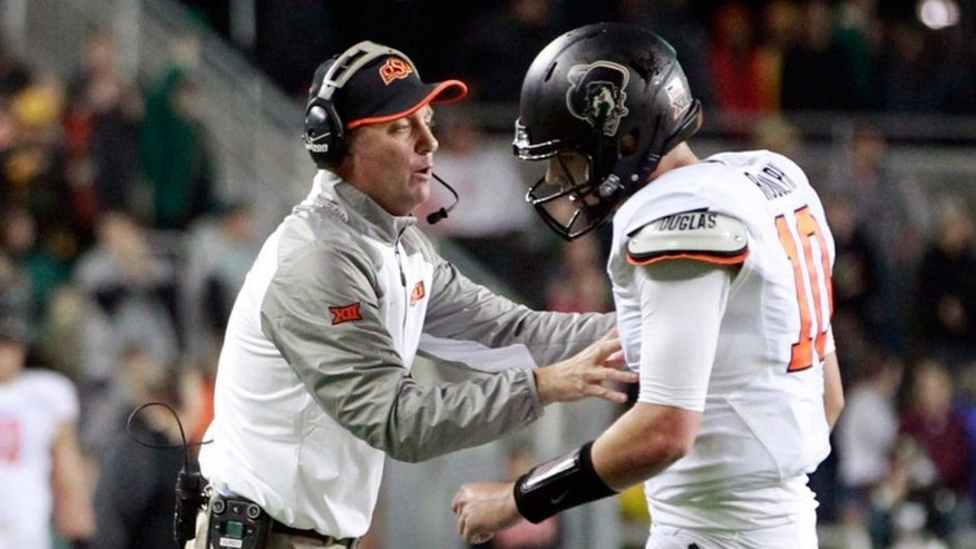 Nov 22, 2014; Waco, TX, USA; Oklahoma State Cowboys head coach Mike Gundy talks with quarterback Mason Rudolph (10) during a time out in the second quarter against the Baylor Bears at McLane Stadium. Mandatory Credit: Tim Heitman-USA TODAY Sports