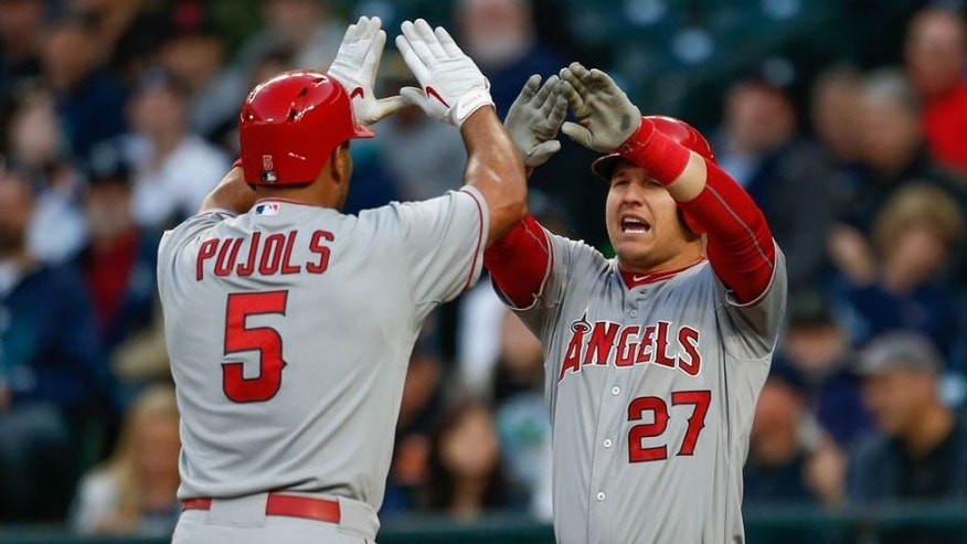 SEATTLE, WA - APRIL 08: Albert Pujols #5 of the Los Angeles Angels of Anaheim is congratulated by Mike Trout #27 after hitting a two-run homer in the first inning against the Seattle Mariners at Safeco Field on April 8, 2015 in Seattle, Washington. (Photo by Otto Greule Jr/Getty Images)