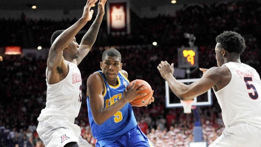 Feb 21, 2015; Tucson, AZ, USA; UCLA Bruins forward Kevon Looney (5) drives to the basket as he is defended by Arizona Wildcats forward Rondae Hollis-Jefferson (23) and forward Stanley Johnson (5) during the first half at McKale Center. Mandatory Credit: Casey Sapio-USA TODAY Sports