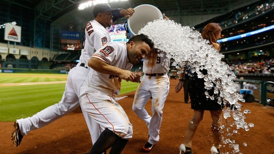 Houston Astros' Jose Altuve (27) gets dunked by Luis Valbuena (18) and Marwin Gonzalez, right, after hitting the game-winning home run in the ninth inning of a baseball game against the Boston Red Sox at Minute Maid Park on Thursday, July 23, 2015, in Houston. The Astros won 5-4. (Karen Warren/Houston Chronicle via AP) MANDATORY CREDIT