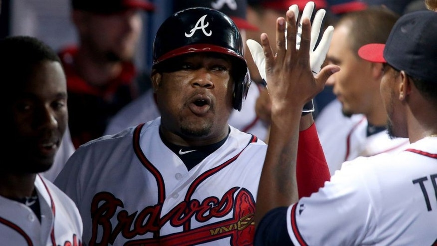 Jul 1, 2015; Atlanta, GA, USA; Atlanta Braves third baseman Juan Uribe (2) celebrates with teammates after hitting a sole home run in the fourth inning of their game against the Washington Nationals at Turner Field. Mandatory Credit: Jason Getz-USA TODAY Sports