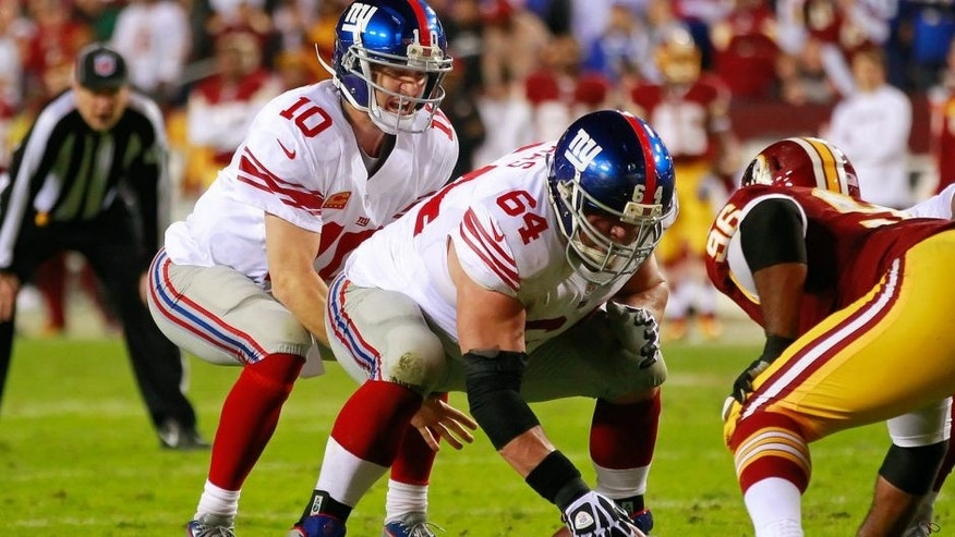 December 3, 2012; Landover, MD, USA; New York Giants quarterback Eli Manning (10) prepares to take a snap from Giants center David Baas (64) against the Washington Redskins at FedEx Field. Mandatory Credit: Geoff Burke-USA TODAY Sports