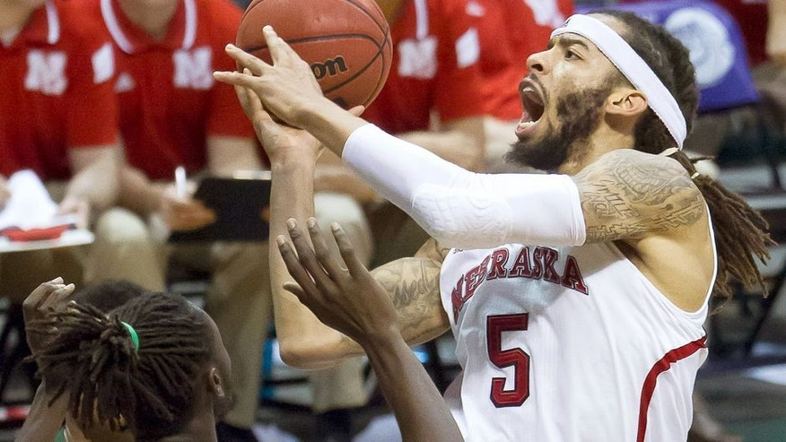 Nebraska forward Terran Petteway (5) drives down the lane with the basketball while defended by Ohio forward Maurice Ndour (5) in the second half of an NCAA college basketball game at the Diamond Head Classic on Thursday, Dec. 25, 2014, in Honolulu. Nebraska defeated Ohio 71-58. (AP Photo/Eugene Tanner)