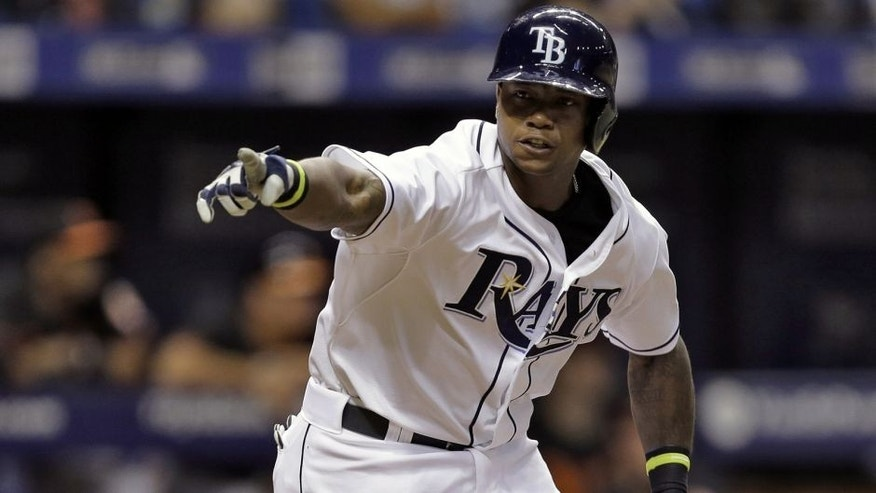 Tampa Bay Rays' Tim Beckham points into the dugout as he runs to first base after hitting a two-run single off Baltimore Orioles relief pitcher Darren O'Day during the eighth inning of a baseball game Friday, July 24, 2015, in St. Petersburg, Fla. Rays' John Jaso and Evan Longoria scored on the play. (AP Photo/Chris O'Meara)