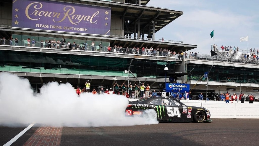 Kyle Busch does a burnout on the front straight after winning the NASCAR Xfinity Series auto race at Indianapolis Motor Speedway in Indianapolis, Saturday, July 25, 2015. (AP Photo/Rob Baker)