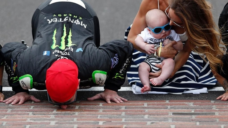 Kyle Busch, left, kisses the yard of bricks next to his wife, Samantha, right, and son, Brexton, after winning the NASCAR Xfinity Series auto race at Indianapolis Motor Speedway in Indianapolis, Saturday, July 25, 2015. (AP Photo/Rob Baker)