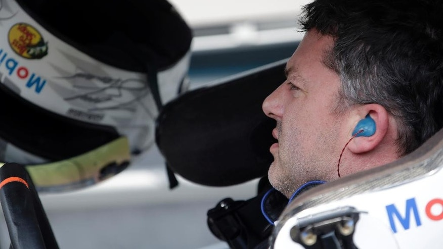 Sprint Cup Series driver Tony Stewart (14) sits in his car during qualifying for the NASCAR Brickyard 400 auto race at Indianapolis Motor Speedway in Indianapolis, Saturday, July 25, 2015. (AP Photo/AJ Mast)