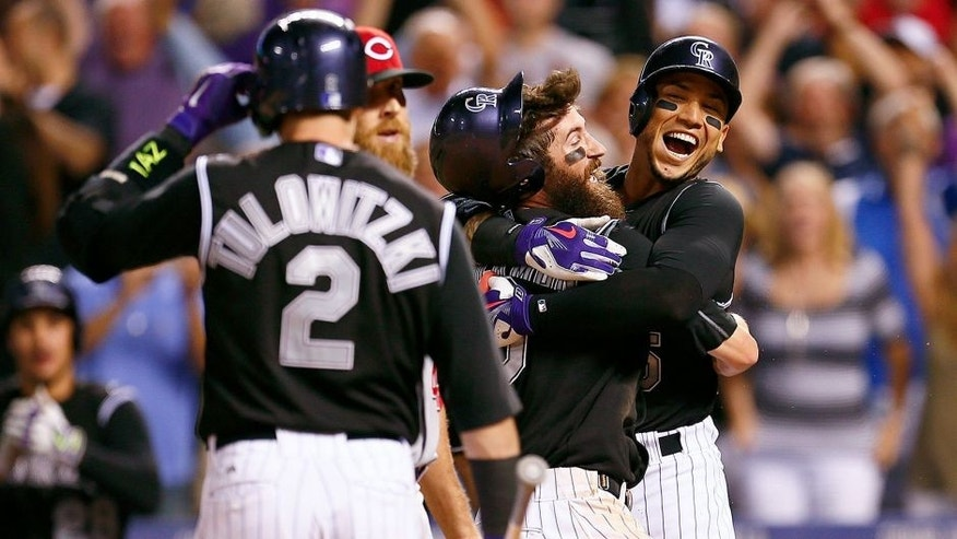 Jul 24, 2015; Denver, CO, USA; Colorado Rockies right fielder Carlos Gonzalez (5) hugs center fielder Charlie Blackmon (19) after his game winning run in the ninth inning against the Cincinnati Reds at Coors Field. Mandatory Credit: Isaiah J. Downing-USA TODAY Sports