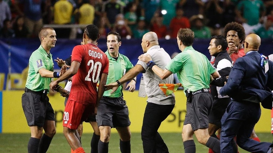 Panama's Anibal Godoy (20) approaches referee Mark Geiger, left, as officials rush in to protect him at the conclusion of a CONCACAF Gold Cup soccer semifinal between Panama and Mexico on Wednesday, July 22, 2015, in Atlanta. Mexico won 2-1. (AP Photo/David Goldman)