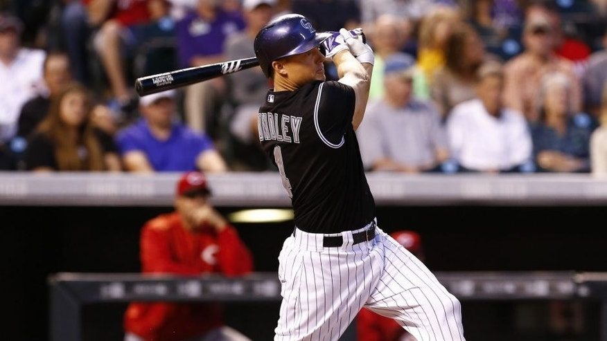 Jul 24, 2015; Denver, CO, USA; Colorado Rockies catcher Nick Hundley (4) hits an RBI triple in the fifth inning against the Cincinnati Reds at Coors Field.