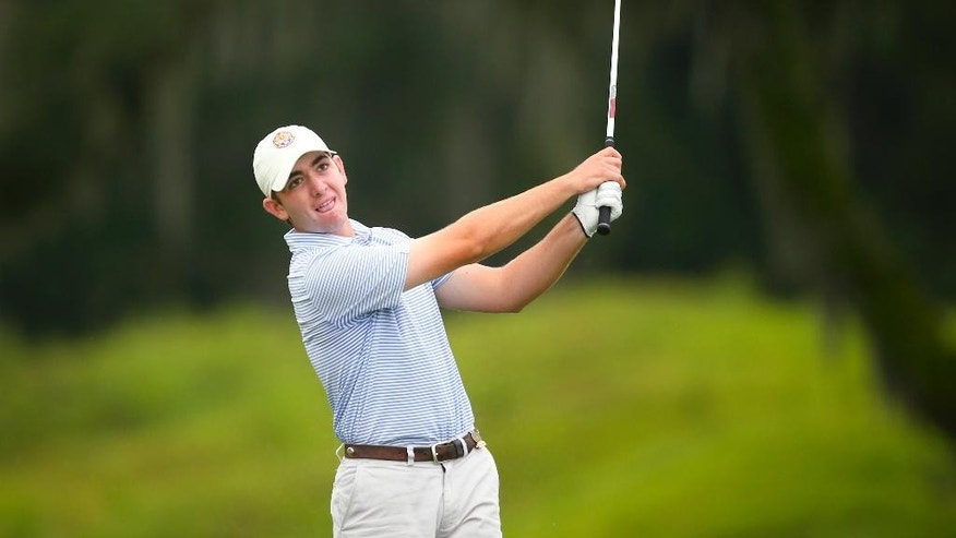 In a photo provided by the USGA, Philip Barbaree watches his second shot on the ninth hole during match play at the U.S. Junior Amateur golf tournament at Colleton River Plantation Club in Bluffton, S.C., on Friday, July 24, 2015. (Darren Carroll/USGA via AP)