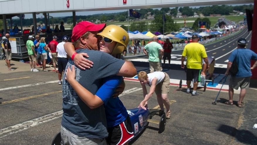 Paige Dewrock of Cape Girardeau, Mo., gets a good luck hug from her dad, Danny before her Local Stock Division heat in the First Energy All-American Soap Box Derby, in Akron, Ohio,  Saturday, July 25, 2015. (AP Photo/Phil Long)