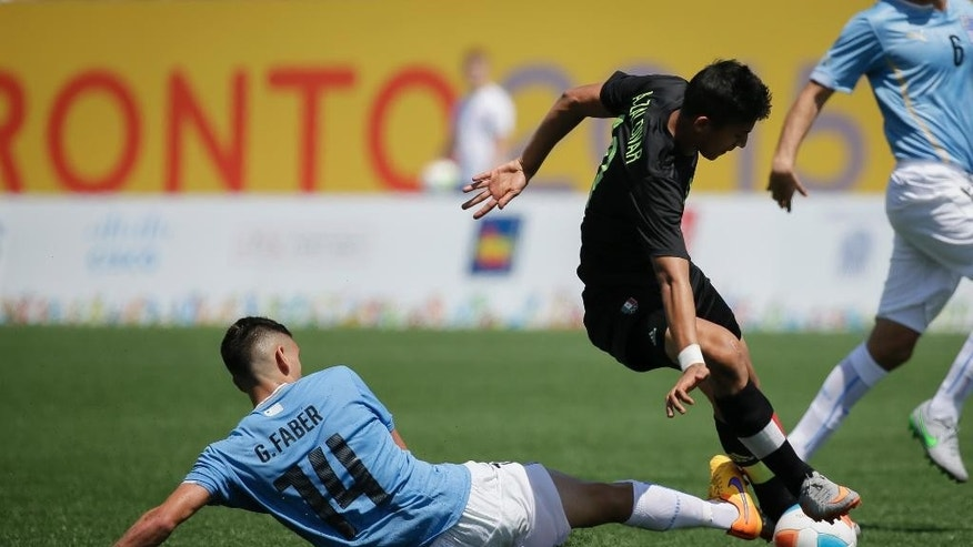 Uruguay's Gaston Faber, left, fights for the ball with Mexico's Angel Zaldivar during the men's gold medal soccer match at the Pan Am Games in Hamilton, Ontario, Sunday, July 26, 2015. (AP Photo/Felipe Dana)