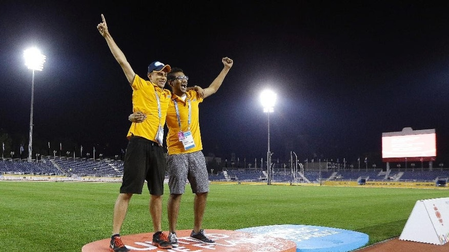Pan Am Games workers Maheyer Shroff, left, and Nishal Shah pose for a souvenir photo on the gold medal award stand after the track and field events ended early Sunday morning, July 26, 2015, in Toronto. The closing ceremony for the games is scheduled to be held Sunday night. (AP Photo/Mark Humphrey)