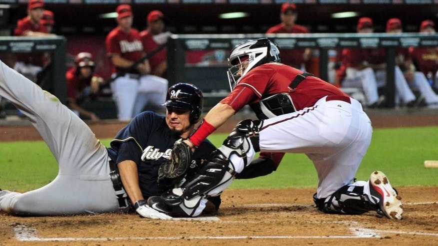 Jul 26, 2015; Phoenix, AZ, USA; Arizona Diamondbacks catcher Oscar Hernandez (right) tags out Milwaukee Brewers starting pitcher Matt Garza during the third inning at Chase Field.
