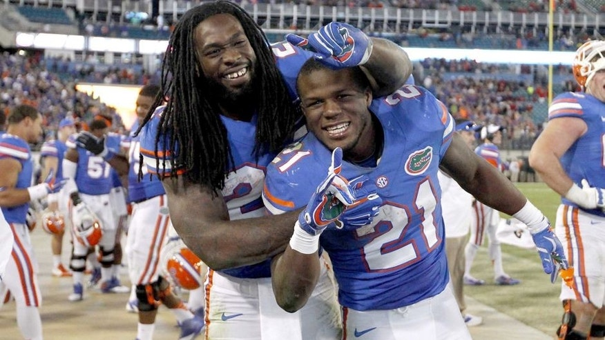 Nov 1, 2014; Jacksonville, FL, USA; Florida Gators running back Kelvin Taylor (21) and running back Matt Jones (24) celebrate during the fourth quarter against the Georgia Bulldogs at EverBank Field. Florida Gators defeated the Georgia Bulldogs 38-20. Mandatory Credit: Kim Klement-USA TODAY Sports