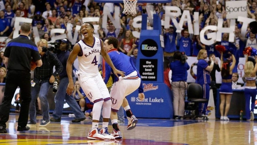 Kansas guard Devonte Graham (4) celebrates following an NCAA college basketball game against West Virginia at Allen Fieldhouse in Lawrence, Kan., Tuesday, March 3, 2015. Kansas defeated West Virginia 76-69 in overtime. Kansas claimed its 11th consecutive Big 12 rchampionship. (AP Photo/Orlin Wagner)