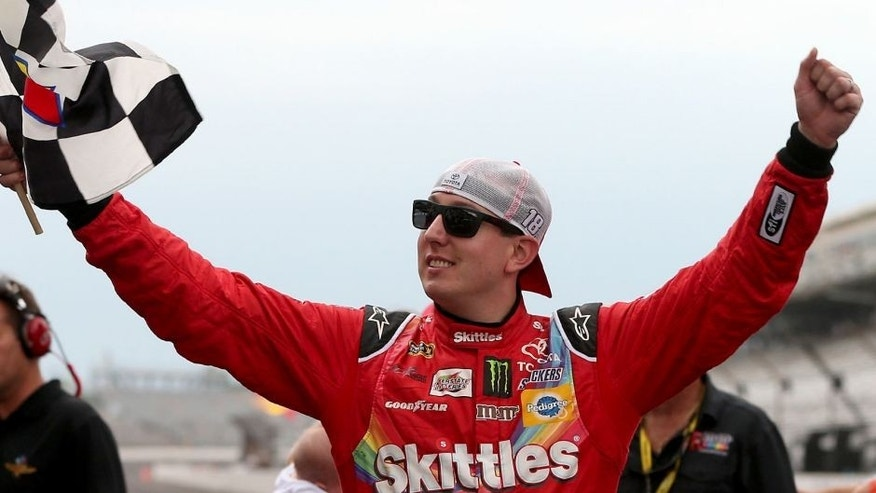 INDIANAPOLIS, IN - JULY 26: Kyle Busch, driver of the #18 Skittles Toyota, celebrates with the checkered flag after winning the NASCAR Sprint Cup Series Crown Royal Presents the Jeff Kyle 400 at the Brickyard at Indianapolis Motor Speedway on July 26, 2015 in Indianapolis, Indiana. (Photo by Brian Lawdermilk/Getty Images)