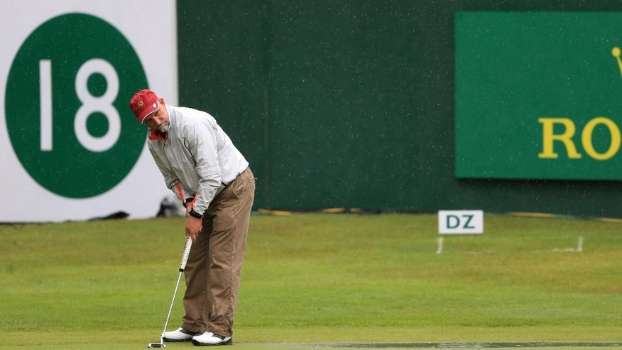USA's Marco Dawson putts on the 18th green during his third round after standing water was cleared, during day four of the Senior Open Championships at Sunningdale Golf Club, England, Sunday July 26, 2015.  Diluvial weather has settled on much of England over the past few days, causing widespread disruption to road systems and sporting events. (Nigel French  / PA via AP) UNITED KINGDOM OUT - NO SALES - NO ARCHIVES