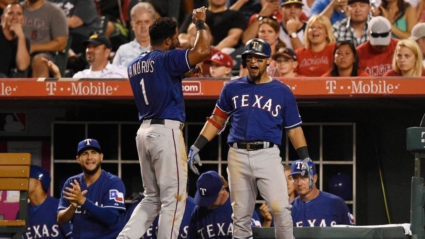Jul 25, 2015; Anaheim, CA, USA; Texas Rangers second baseman Rougned Odor (12) and Texas Rangers shortstop Elvis Andrus (1) react after a run scored by Texas Rangers first baseman Mitch Moreland (not pictured) during the eighth inning against the Los Angeles Angels at Angel Stadium of Anaheim. Mandatory Credit: Kelvin Kuo-USA TODAY Sports