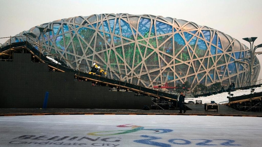 "FOR STORY OLYMPICS 2022 BID - FILE - In this Dec. 26, 2014 file photo, a worker walks past an ice rink with the logo for Beijing's Winter Olympics bid ahead of a countdown event to the new year in front of the iconic Beijing National Stadium ""Bird's Nest"" in Beijing. The International Olympic Committee will be faced with two starkly different choices, Beijing and Almaty, Kazakhstan , when it selects the host city for the 2022 Winter Games, on July 31 in Kuala Lumpur, Malaysia. (AP Photo/Ng Han Guan, File)"