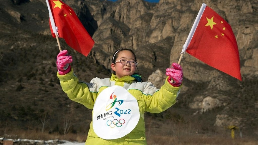 FOR STORY OLYMPICS 2022 BID - FILE - In this Friday, Jan. 16, 2015 file photo, a Chinese girl waves the national flags, wearing the 2022 Olympic bid logo to show her support at the ski resort in Yanqing, a suburb of Beijing, where the speed mavens of Alpine skiing and the sliding events - bobsled, skeleton and luge - have been proposed to be held in the bid for the 2022 Winter Olympics. The International Olympic Committee will be faced with two starkly different choices, Beijing and Almaty, Kazakhstan , when it selects the host city for the 2022 Winter Games, on July 31 in Kuala Lumpur, Malaysia.  (AP Photo/Ng Han Guan, File)