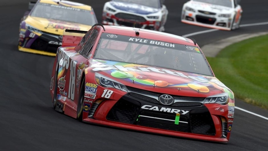 INDIANAPOLIS, IN - JULY 26: Kyle Busch, driver of the #18 Skittles Toyota, leads a pack of cars during the NASCAR Sprint Cup Series Crown Royal Presents the Jeff Kyle 400 at the Brickyard at Indianapolis Motor Speedway on July 26, 2015 in Indianapolis, Indiana. (Photo by Rainier Ehrhardt/NASCAR via Getty Images)