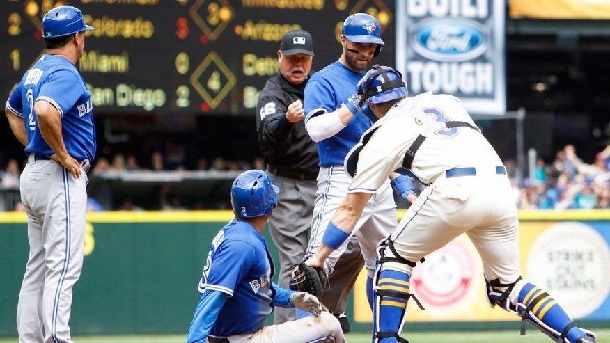 Jul 26, 2015; Seattle, WA, USA; Toronto Blue Jays left fielder Ezequiel Carrera (3) is tagged out by Seattle Mariners catcher Mike Zunino (3) for the final out of the fourth inning in front of center fielder Kevin Pillar (11) and third base as coach Luis Rivera (L) at Safeco Field. Mandatory Credit: Joe Nicholson-USA TODAY Sports
