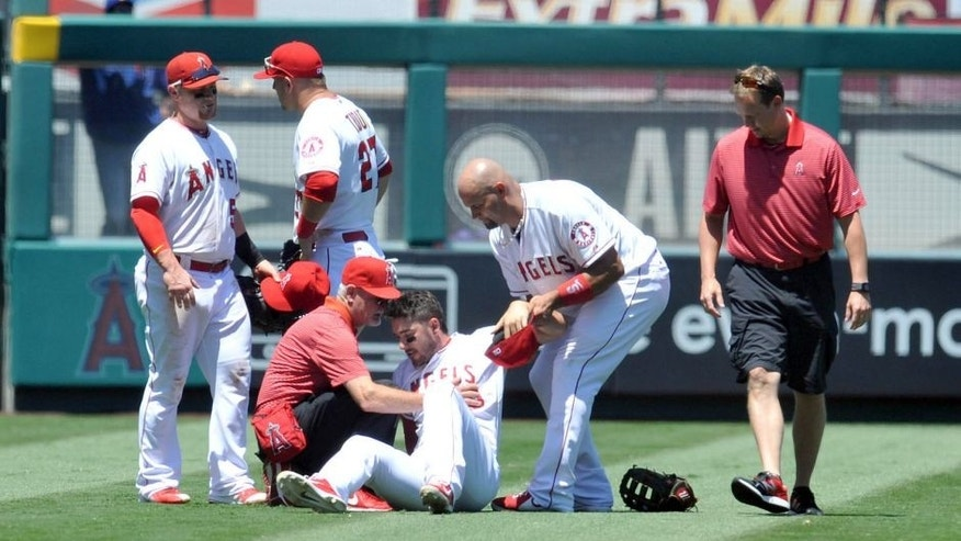 <p>July 26, 2015; Anaheim, CA, USA; Los Angeles Angels left fielder Matt Joyce (20) is helped up by first baseman Albert Pujols (5) and trainer Rick Smith after colliding with shortstop Erick Aybar (2) in the fourth inning against the Texas Rangers at Angel Stadium of Anaheim. Mandatory Credit: Gary A. Vasquez-USA TODAY Sports</p>