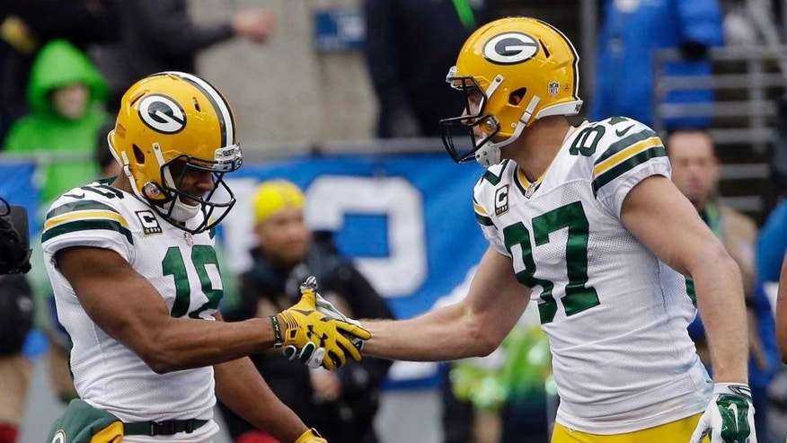 The Green Bay Packers' Randall Cobb (left) celebrates his touchdown catch with Jordy Nelson during the first half of the NFC championship game in Seattle.