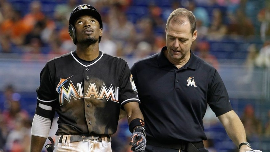 Miami Marlins' Dee Gordon, left, walks off the field with head trainer Sean Cunningham, right, after sliding safely into first in seventh inning of a baseball game against the Cincinnati Reds, Saturday, July 11, 2015, in Miami. The Marlins defeated the Reds 14-3. (AP Photo/Lynne Sladky)
