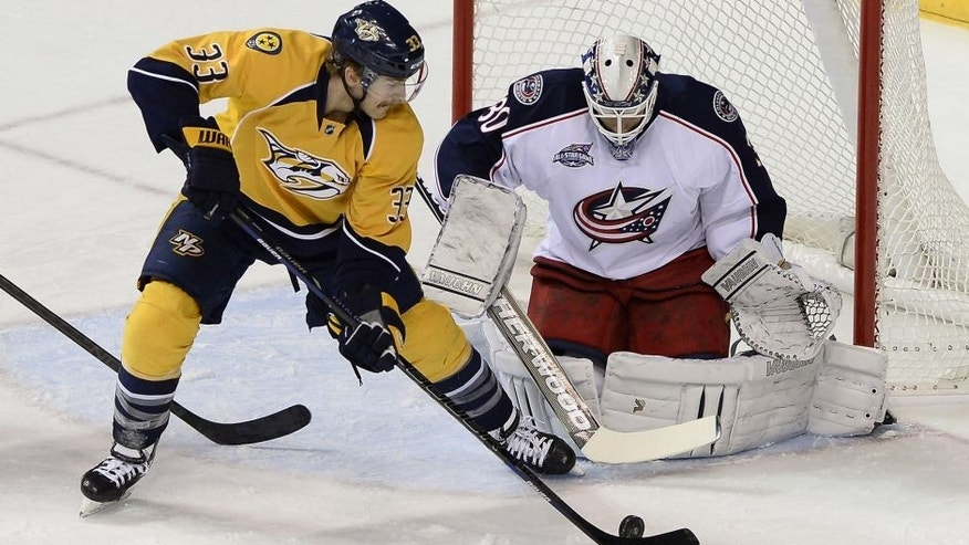 Columbus Blue Jackets goalie Curtis McElhinney (30) blocks a shot by Nashville Predators center Colin Wilson (33) in the first period of an NHL hockey game Saturday, Nov. 29, 2014, in Nashville, Tenn. (AP Photo/Mark Zaleski)