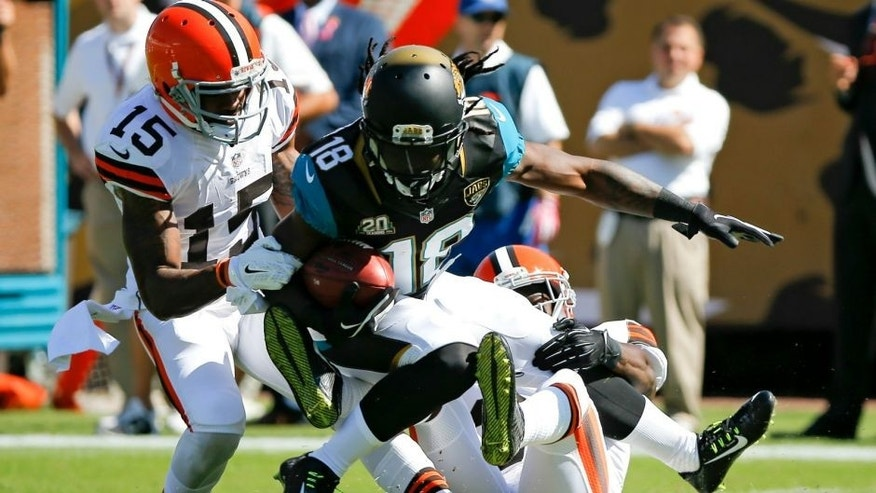 <p>Jacksonville Jaguars' Ace Sanders (18) is brought down by Cleveland Browns wide receiver Marlon Moore (15) and cornerback Johnson Bademosi, right, during the first half of an NFL football game in Jacksonville, Fla., Sunday, Oct. 19, 2014. (AP Photo-Stephen B. Morton)</p>