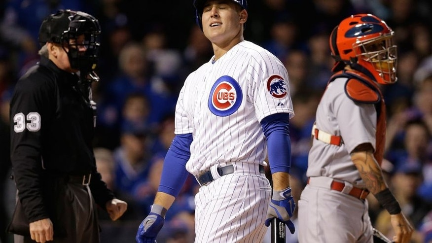 Chicago Cubs' Anthony Rizzo, center, reacts after being called out on strikes during the first inning of a Major League Baseball season-opening game against the St. Louis Cardinals in Chicago, Sunday, April 5, 2015. (AP Photo/Nam Y. Huh)