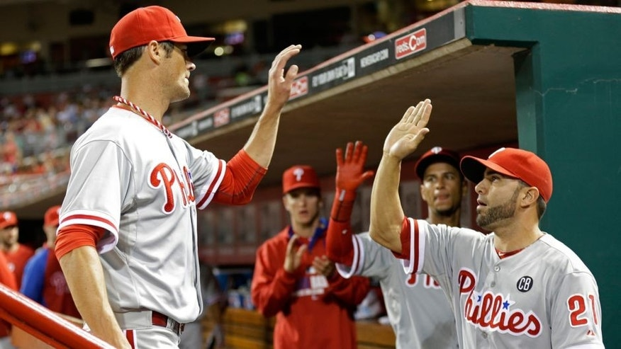 Philadelphia Phillies starting pitcher Cole Hamels, left, is congratulated by Wil Nieves (21) after he was taken out in the eighth inning of a baseball game against the Cincinnati Reds, Friday, June 6, 2014, in Cincinnati. Hamels was the winning pitcher in the game won by Philadelphia 8-0. (AP Photo/Al Behrman)