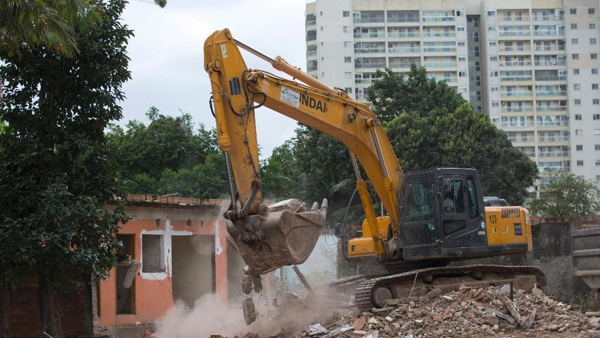 In this July 23, 2015 photo, a heavy machinery load  debris from a demolished house at the Vila Autodromo slum, in Rio de Janeiro, Brazil, Thursday, July 23, 2015. It will take years to know if the Olympics improved life for 12 million Cariocas, as Rio residents are known. And if so, who profited the most from spending $12 billion in public and private money: ordinary people, politicians, or private real estate developers and construction companies? (AP Photo/Silvia Izquierdo)