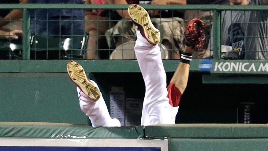 <p>Boston Red Sox center fielder Mookie Betts flips over the bullpen wall while trying to field a drive by Chicago White Sox's Jose Abreu during the sixth inning of a baseball game at Fenway Park in Boston, Tuesday, July 28, 2015. Umpires ruled the play a home run after video replay review. (AP Photo/Charles Krupa)</p>