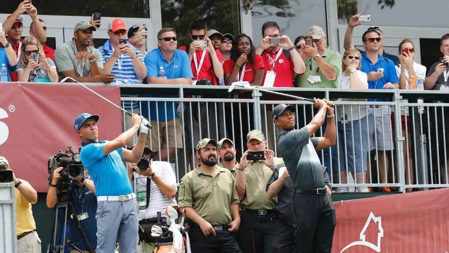 Rickie Fowler, left, and Tiger Woods hit simultaneous tee shots on a par three to benefit the Military Warriors Support Foundation during the pro-am for the Quicken Loans National Golf tournament at the Robert Trent Jones Golf Club in Gainesville, Va., Wednesday, July 29, 2015.  If either had made a hole in one $25,000 would have been donated to the MWSF.   (AP Photo/Steve Helber)