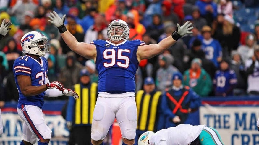 Dec 22, 2013; Orchard Park, NY, USA; Buffalo Bills defensive tackle Kyle Williams (95) celebrates a sack on Miami Dolphins quarterback Ryan Tannehill (17) during the second half at Ralph Wilson Stadium. Buffalo beats Miami 19-0. Mandatory Credit: Timothy T. Ludwig-USA TODAY Sports