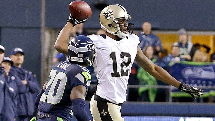New Orleans Saints wide receiver Marques Colston (12) throws the ball after catching a pass next to Seattle Seahawks cornerback Jeremy Lane (20) during the fourth quarter of an NFC divisional playoff NFL football game in Seattle, Saturday, Jan. 11, 2014. The Seahawks won 23-15. Instead of stepping out of bounds to have one more play, Colston tried to throw across the field to Darren Sproles. The pass was forward and the penalty for an illegal forward pass ran off the final 10 seconds of the clock giving Seattle the victory. (AP Photo/Elaine Thompson)
