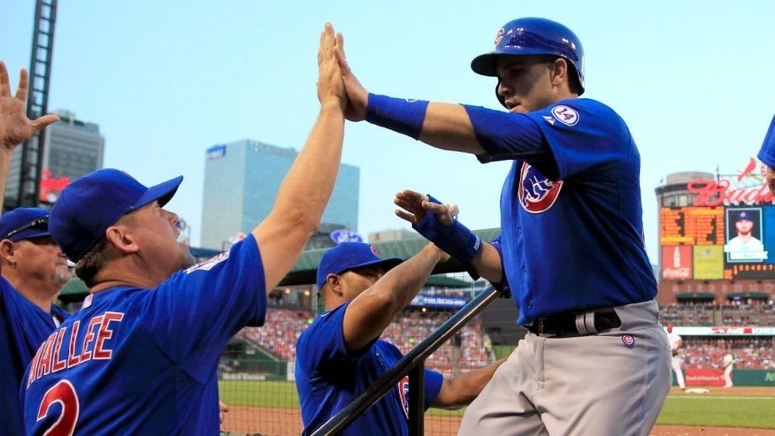 Chicago Cubs' Miguel Montero, right, is congratulated by hitting coach John Mallee, left, after scoring during the first inning of a baseball game against the St. Louis Cardinals, Monday, May 4, 2015, in St. Louis. (AP Photo/Jeff Roberson)