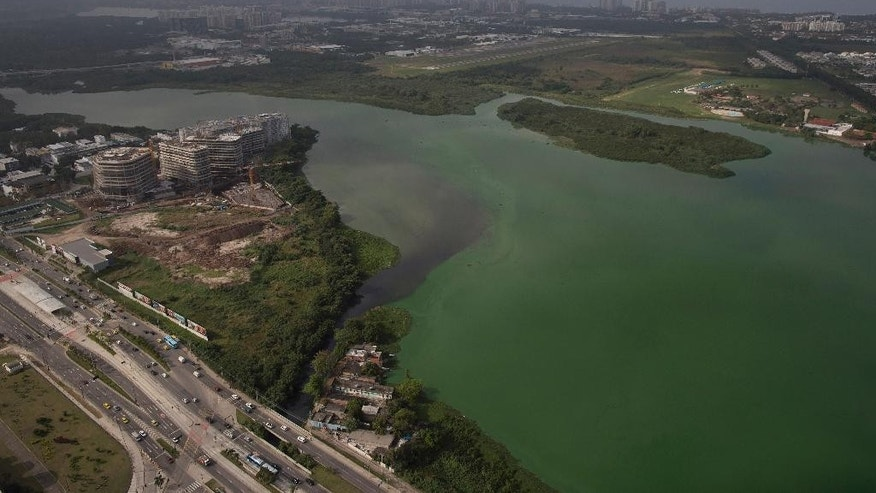 This July 27, 2015 aerial photo shows fluorescent green waters in the Marapendi Lagoon, in Rio de Janeiro, Brazil. The lagoons that hug the Olympic Park and which the government's own data shows are among the most polluted waters in Rio were to be dredged, but the project got hung up in bureaucratic hurdles and has yet to start. (AP Photo/Leo Correa)