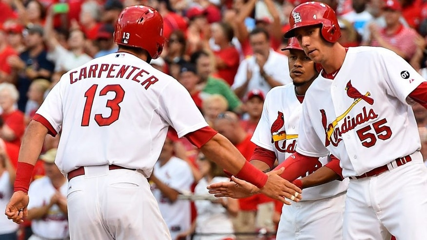 Jul 30, 2015; St. Louis, MO, USA; St. Louis Cardinals third baseman Matt Carpenter (13) celebrates with teammates after hitting a three-run home run off of Colorado Rockies starting pitcher Chris Rusin (not pictured) in the second inning at Busch Stadium. Mandatory Credit: Jasen Vinlove-USA TODAY Sports