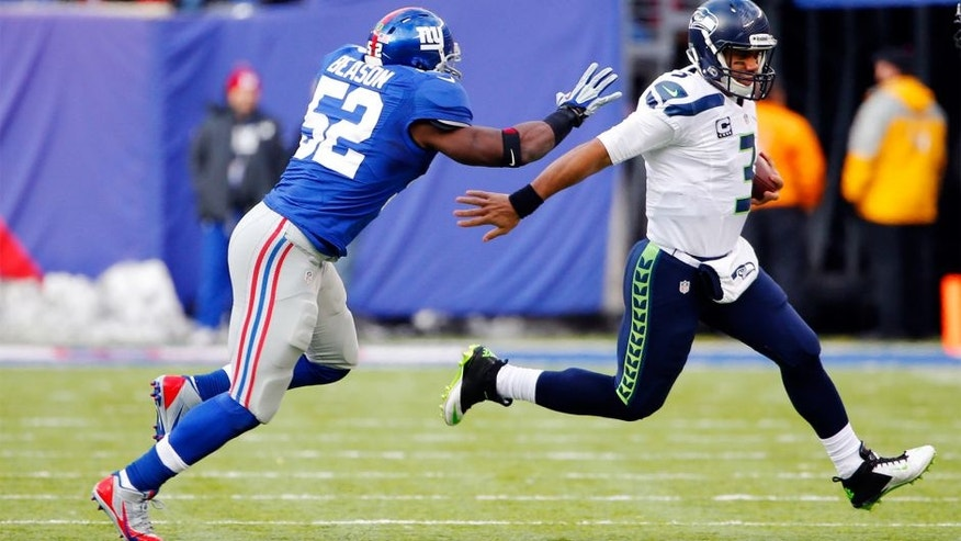 Dec 15, 2013; East Rutherford, NJ, USA; Seattle Seahawks quarterback Russell Wilson (3) gets away from New York Giants middle linebacker Jon Beason (52) during the first half at MetLife Stadium. Mandatory Credit: Jim O'Connor-USA TODAY Sports