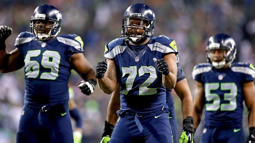 SEATTLE, WA - JANUARY 19: Defensive end Michael Bennett #72 of the Seattle Seahawks and defensive tackle Clinton McDonald #69 react against the San Francisco 49ers during the 2014 NFC Championship at CenturyLink Field on January 19, 2014 in Seattle, Washington. (Photo by Ronald Martinez/Getty Images)